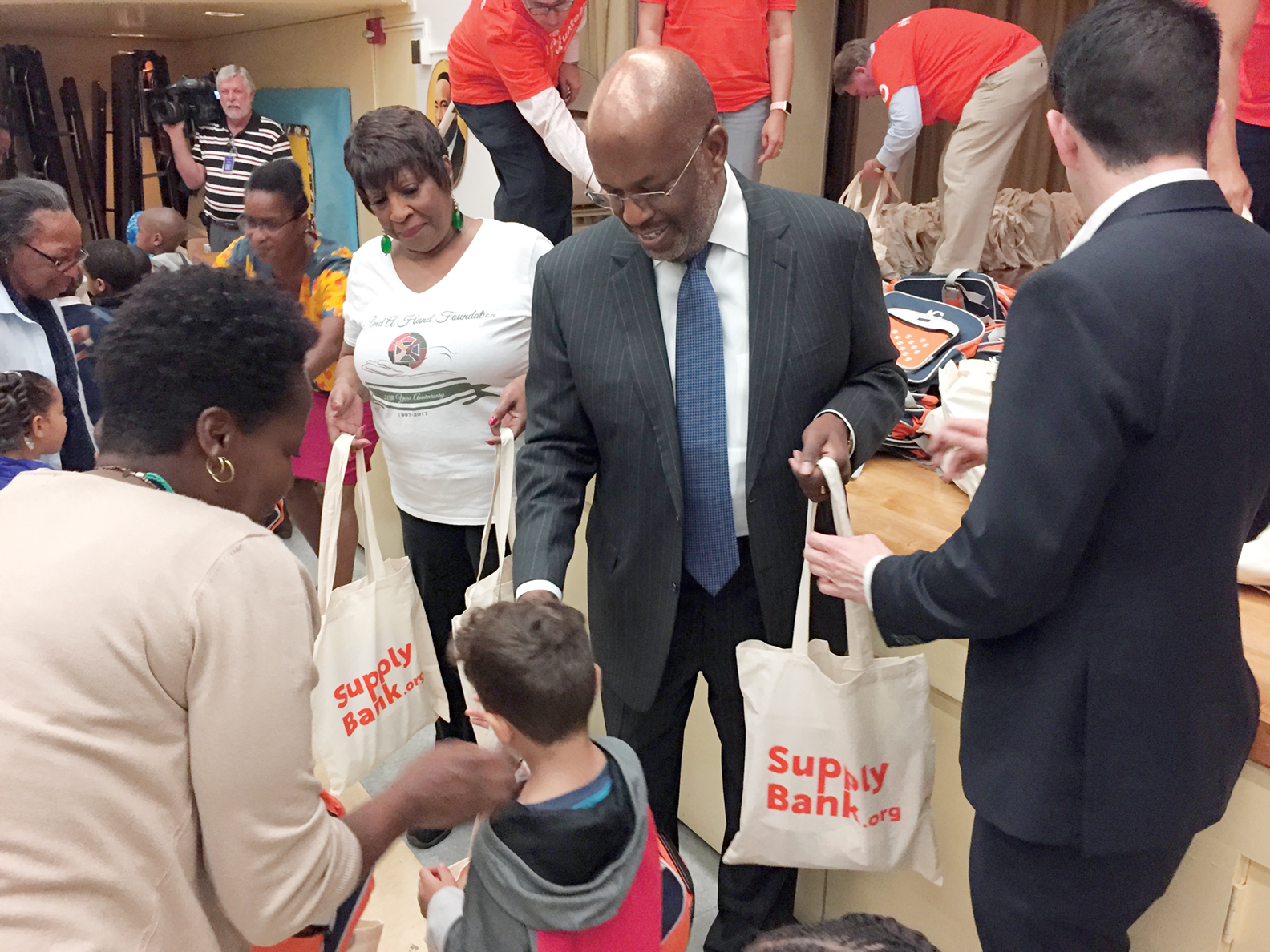 Bernard J. Tyson helps pass out backpacks and school kits to students at Martin Luther King Jr. Elementary School in Oakland.
