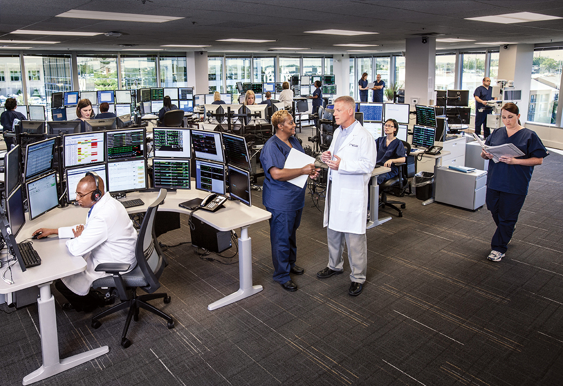 Intensivists, nurses and respiratory therapists remotely monitor ICU patients from a central operations center.