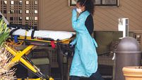 A healthcare worker wearing PPE wheels a bed into a nursing home.