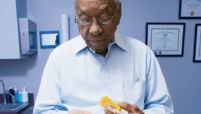 Older man at a doctor's office holding a bottle of pills