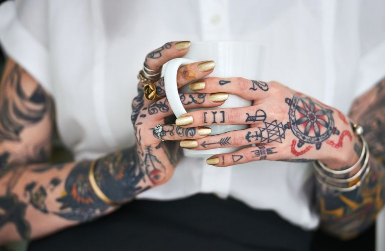 A woman with tattoos on her arms holding a coffee cup.