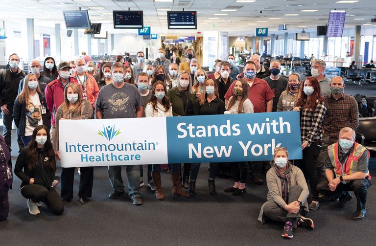 Intermountain caregivers hold up a sign in support of New York City after landing in New York to help.