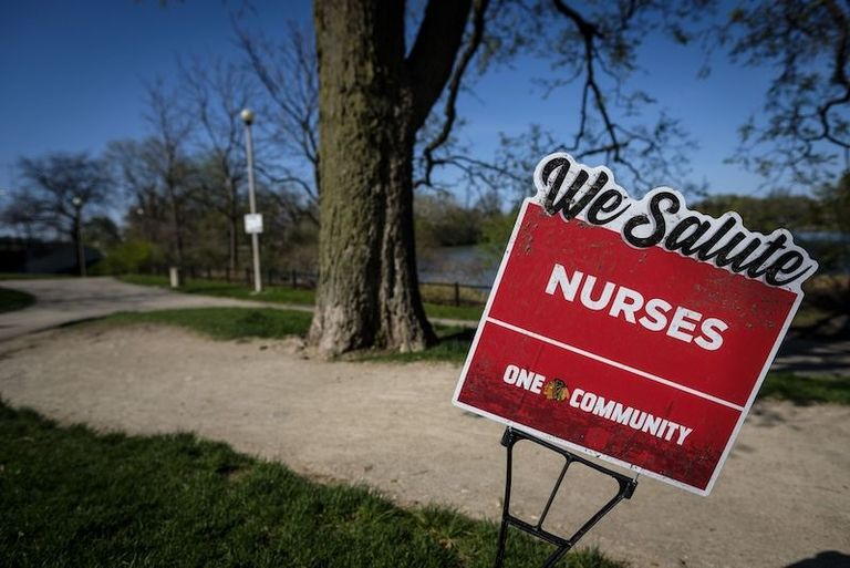 We salute nurses sign in a park.