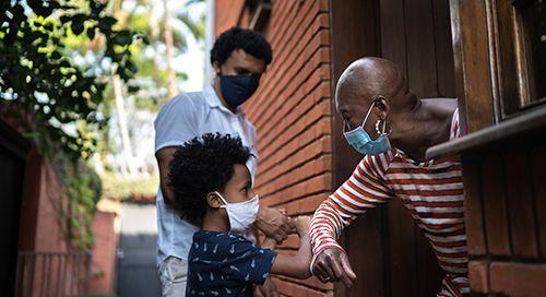 people wearing masks touching arms image