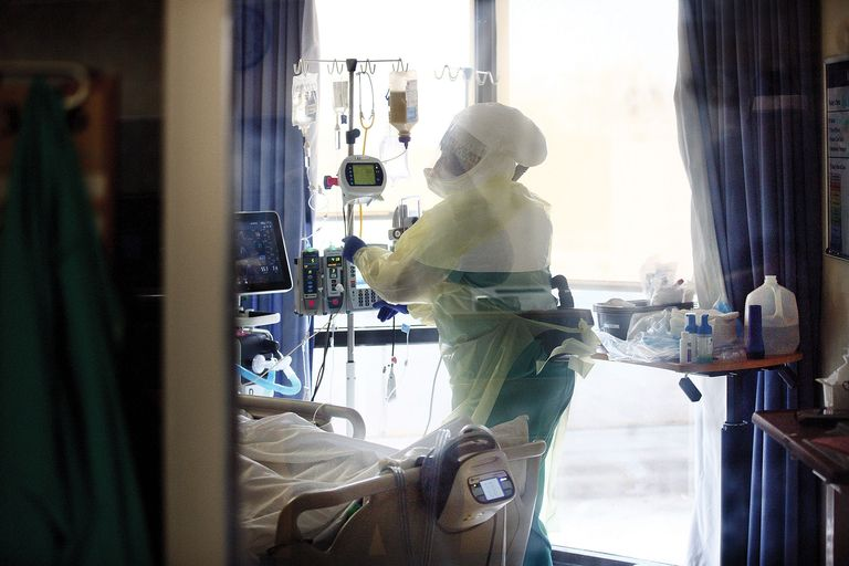 Provider in full protective gear in a patient's room.
