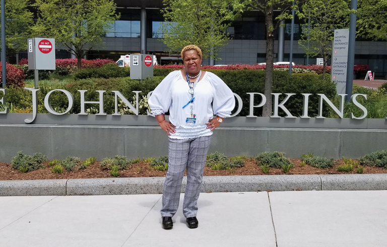 Collie Thomas in front of Johns Hopkins sign
