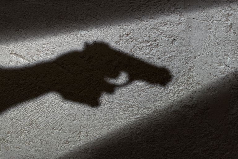 A silhouette of a hand holding a gun.