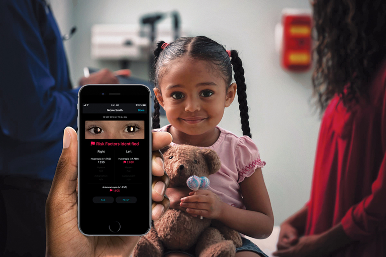 A child being screened for vision problems using a smartphone.