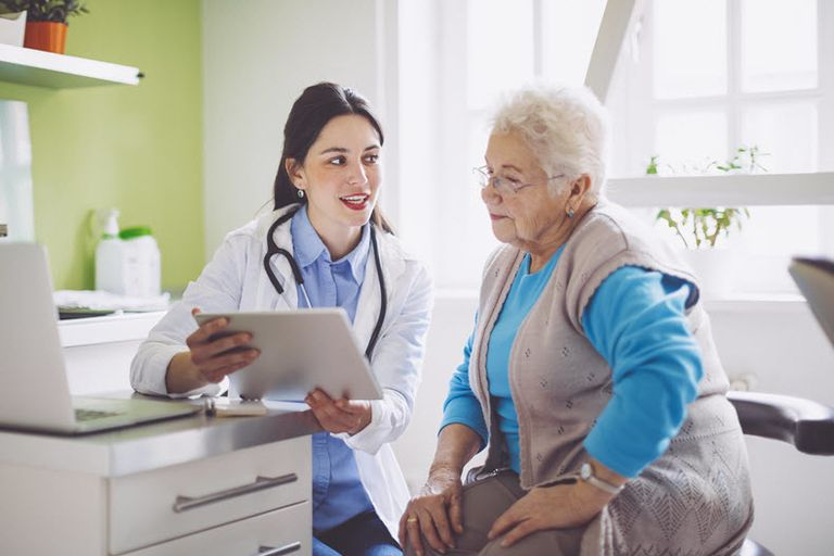 doctor and older patient looking at chart together