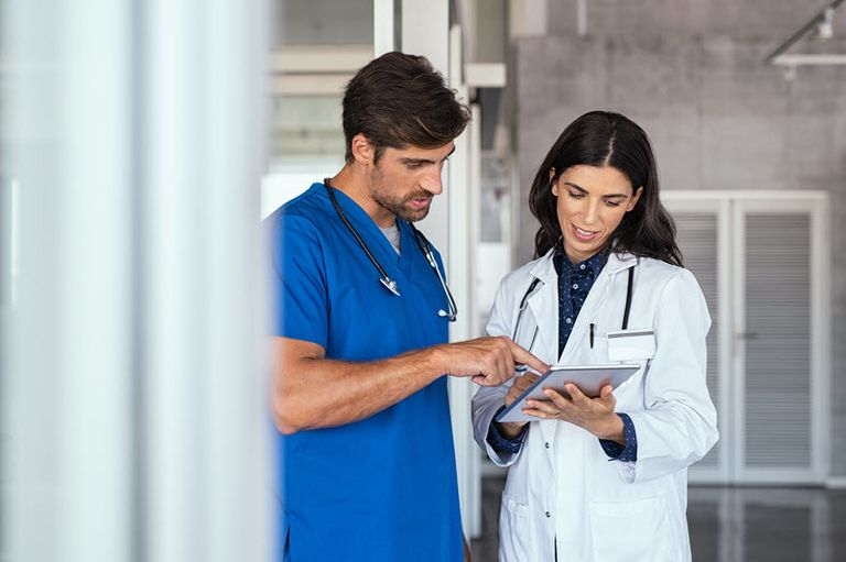 nurse and doctor speaking looking at ipad stock image