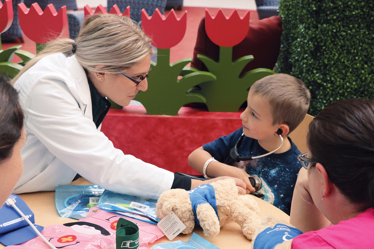 Second-year medical student Alyssa Heintschelassists a pediatric patient with a stethoscope in the care of a teddy bear.
