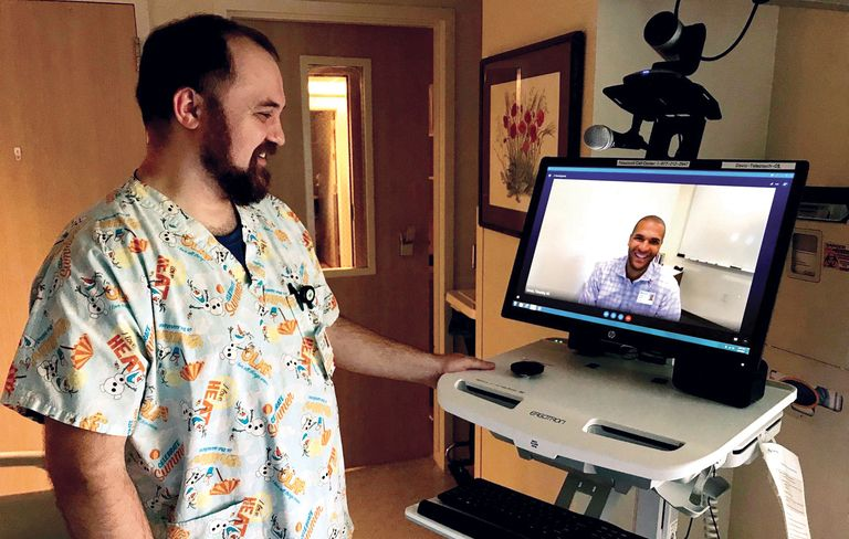 Sean Wade, a registered nurse at Sutter Davis Hospital, demonstrates how a mobile workstation allows patients to connect with psychiatrists from around the country via its telepsychiatry program. On screen is Tim Jones, Sutter Health's telepsychiatry program manager.