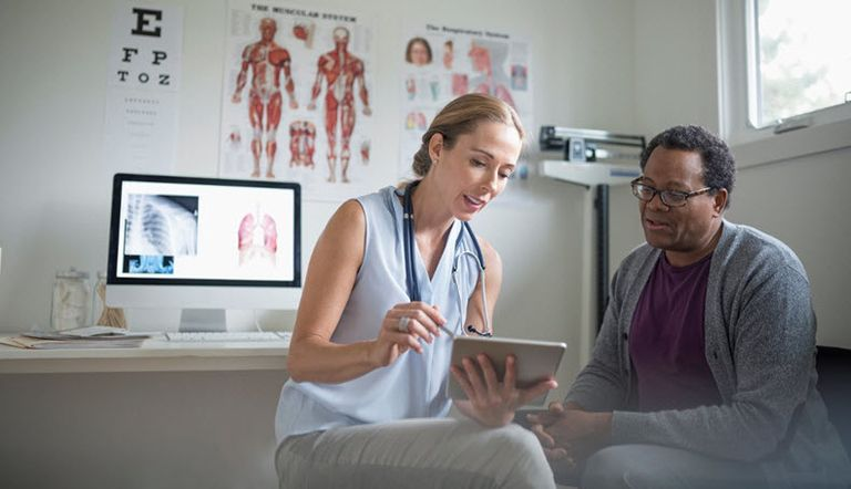 doctor and patient in room looking at ipad