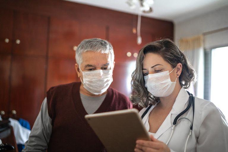 man and woman looking at ipad wearing face masks stock image