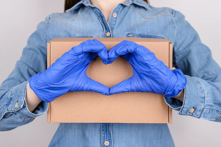 woman holding cardboard box wearing gloves making heart with hands