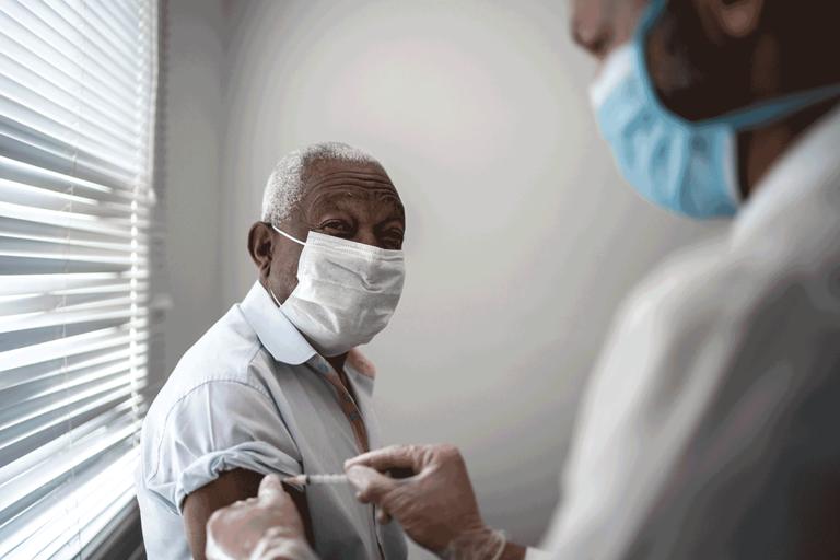An older man wearing a mask receiving a vaccine.