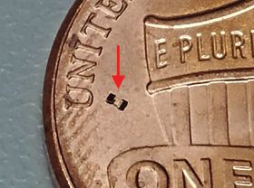 A microbot photographed on top of a penny for scale.