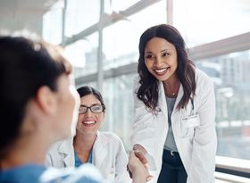 woman doctor shaking hands with nurse and smiling