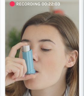 A woman being recorded using her inhaler on a smartphone.