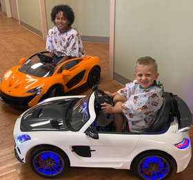 Two patients at Northwest Surgical Hospital driving the mini-cars.