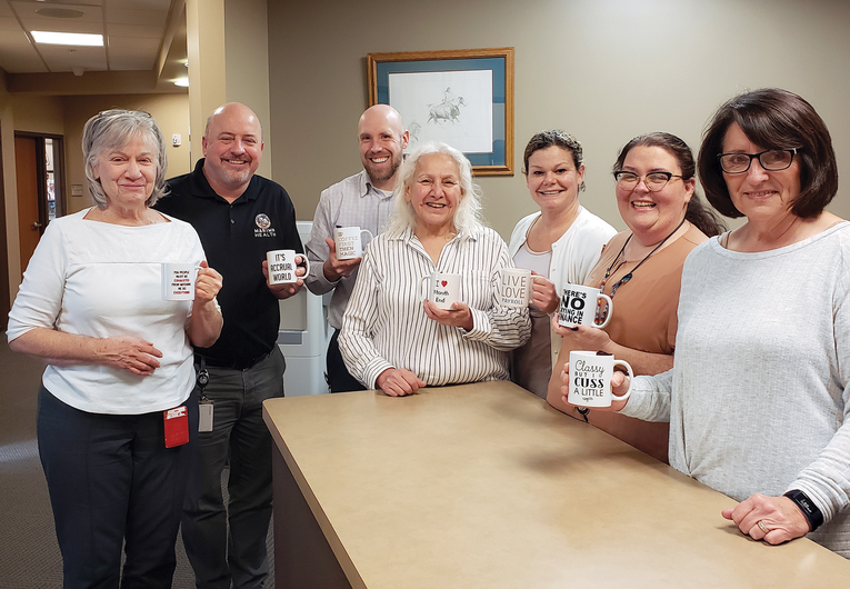 Marimn Health's finance team shows off their custom coffee mugs.