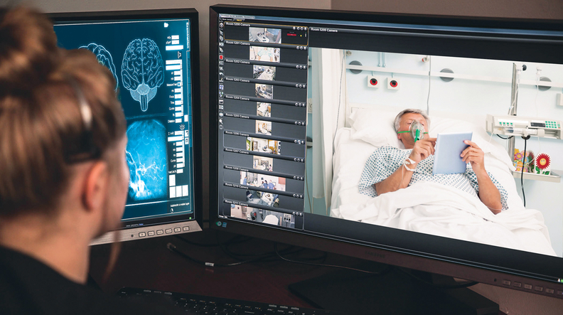 A nurse monitors a patient using a virtual nurses' station.