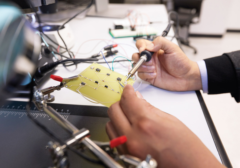 An engineer assembles the electronics for a nerve stimulation device.