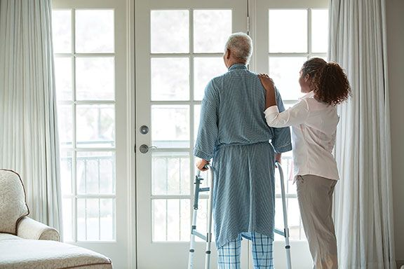 A home health worker with an older man using a walker.