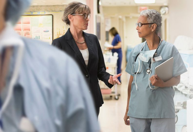 A provider in scrubs with a tablet talking to a woman wearing a suit.