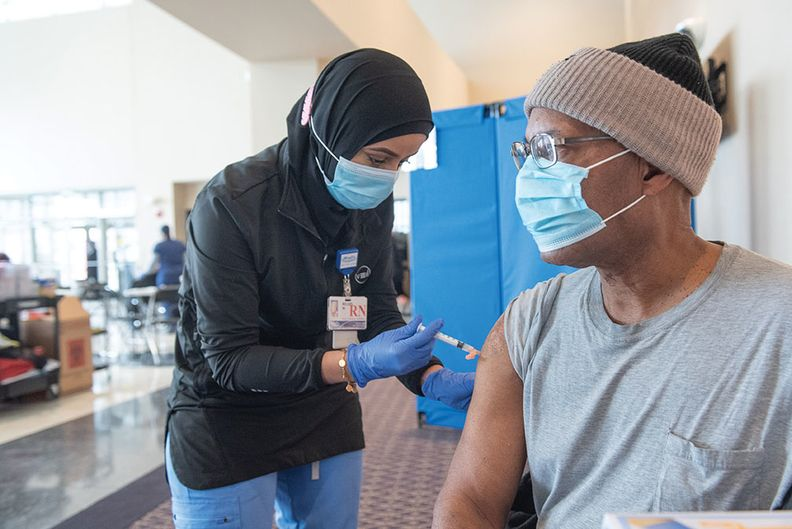 A provider giving a vaccine to a patient.