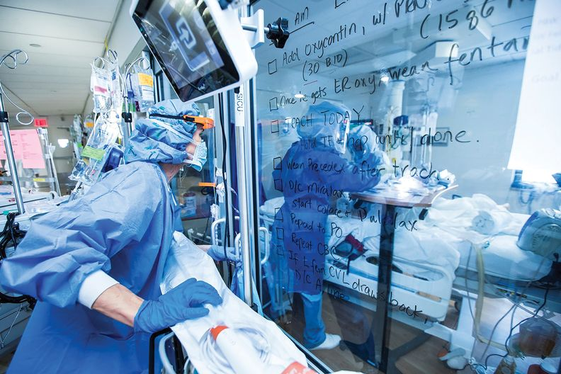A provider wearing PPE looking at a wall with patient notes.