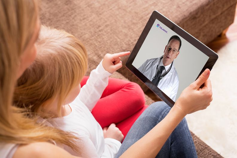 A parent and child talking to a doctor using a tablet.