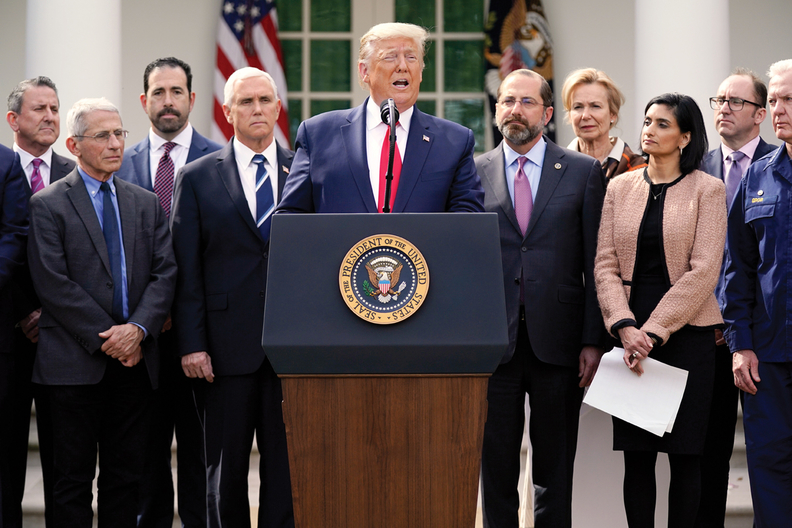 President Donald Trump surrounded by members of the federal COVID-19 team