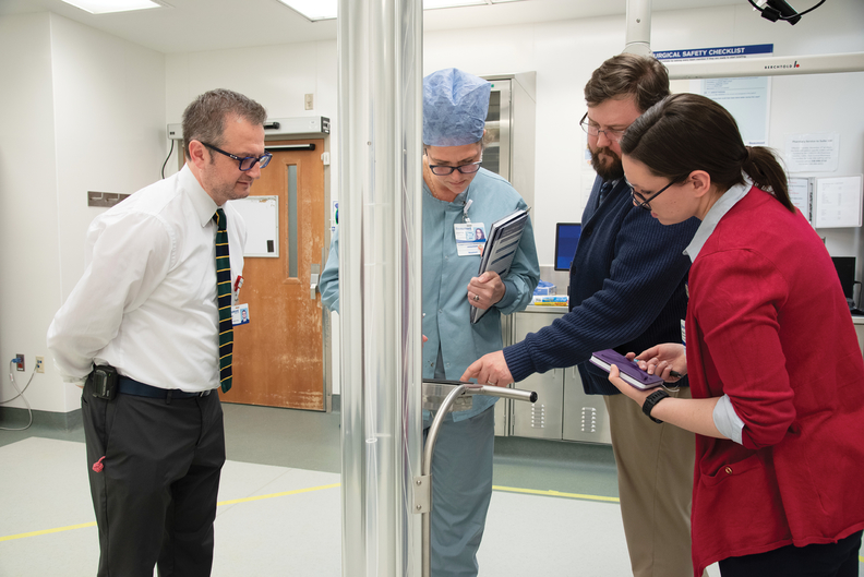 Members of the clinical engineering and central processing teams at Beaumont Health demonstrate the ultraviolet light process being deployed to reuse N95 respirator masks.