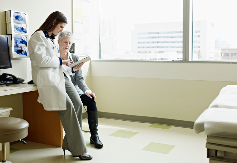 Doctor showing a patient information on a tablet.