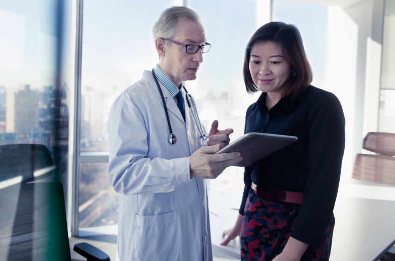Doctor physician with patient standing at window with ipad