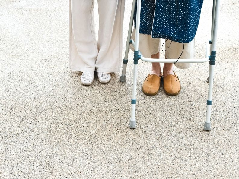 An older woman standing with a long-term care provider.
