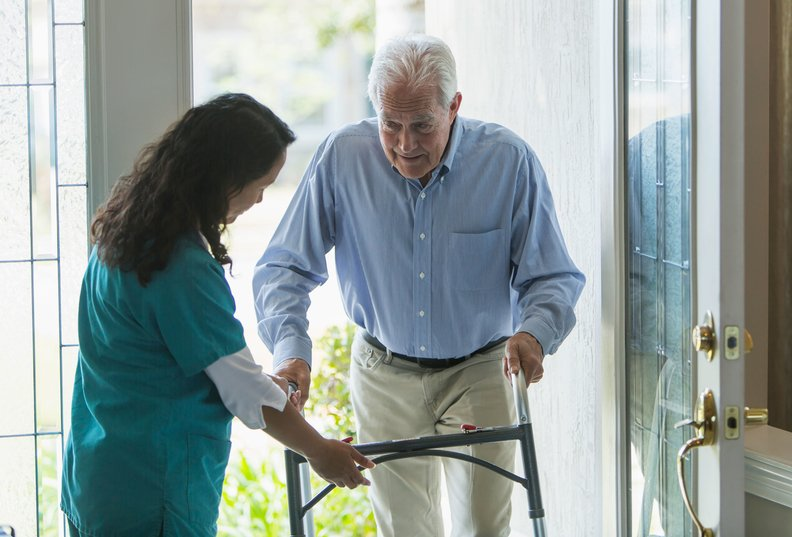 A provider helping an older man with a walker at home.