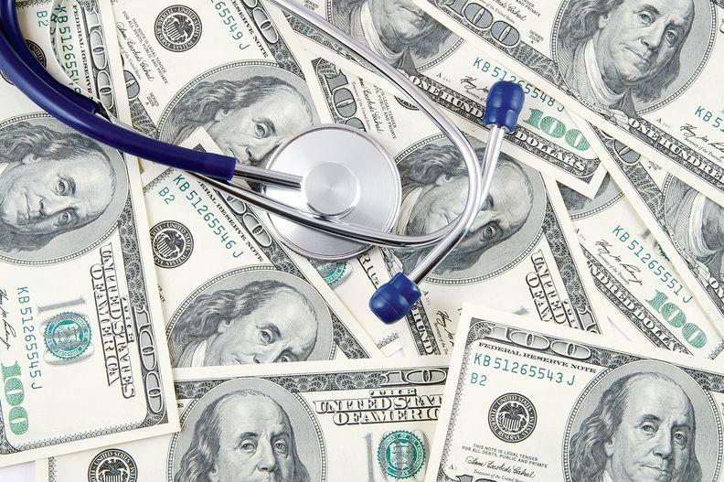 Stethoscope on pile of hundred dollar bills