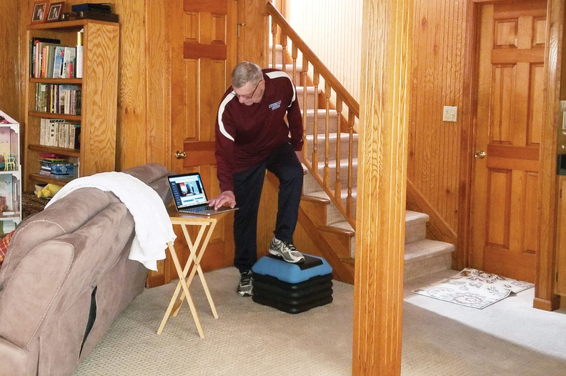 Joseph Baltrusaitis watches a video at home to guide his physical therapy regimen after hip surgery.