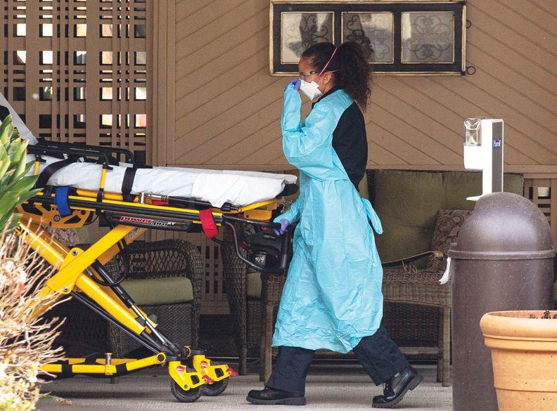 A healthcare worker wearing PPE wheeling an empty gurney.