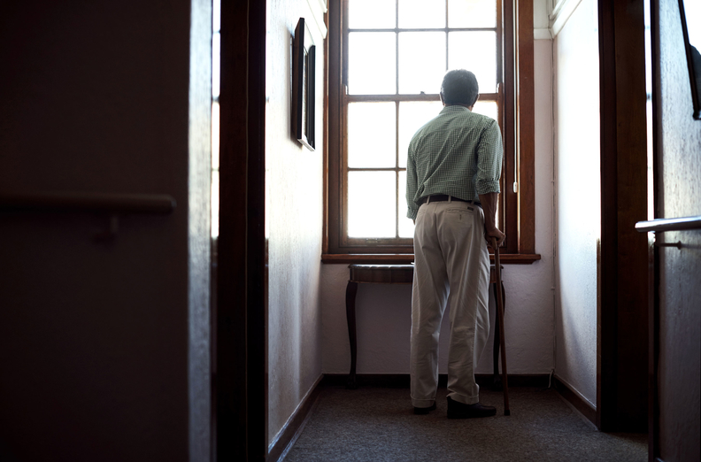Older man using cane looking out a window in his home.